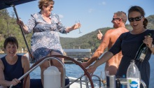 Naked man giving thumbs up signal to woman with a wine glass on the back of a yacht