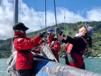 women hoisting sail on Elliott 1050 yacht