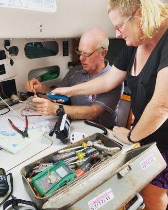 Man and woman doing electrical repairs on board a yacht