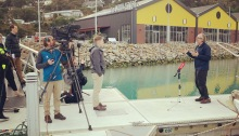 Man doing socially distant TV interview with TVNZ channel 1 news at Te Ana Marina
